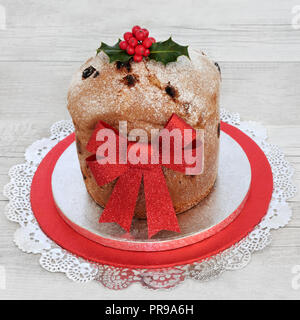 Panettone Christmas cake with red glitter bow and winter holly on rustic wood background. Traditional Italian sweet bread. - Stock Photo