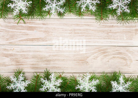 Christmas frame made of fir branches decorated with snowflakes on a light wooden background - Stock Photo