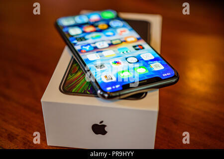 KALAMATA, GREECE - SEPTEMBER 30 2018: Close up photo of the Iphone XS model. The new Apple ten S in black color on a vintage wooden desk - Stock Photo