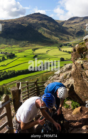 Two climbers gearing up in sunshine in preparation of a climb at Langdale Pikes, Great Langdale, Lake District, Cumbria, England. - Stock Photo