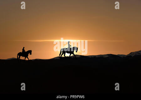 Silhouette of man and woman riding horse across horizon as the sun goes down - Stock Photo