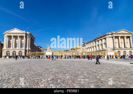 Paris, France - March 14, 2018: Exterior facade of Versailles Palace with tourists waiting the queue to visit it - Stock Photo