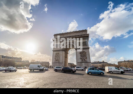 Arc de Triomphe with the busy cobblestone street, on backlight, at sunset - Stock Photo