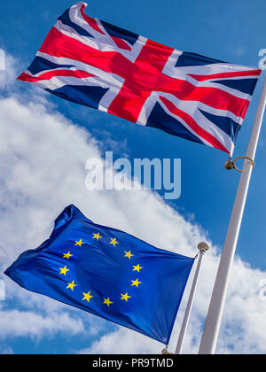 BREXIT UK Union Jack Flag flying high above EU European Flag in a stiff breeze on a sunlit day with blue sky divided by clouds - Stock Photo