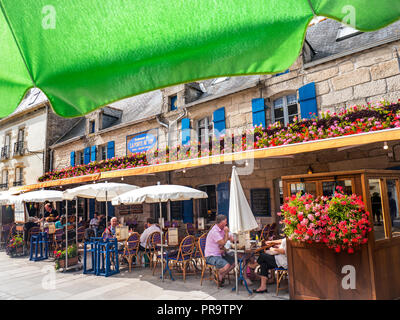 Brittany French Rustic alfresco restaurant 'La Port Au Vin' with floral flowers display and diners Ville Close de Concarneau Bretagne Finistere France - Stock Photo