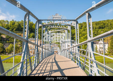 Salzburg, Austria - May 22, 2017: Pedestrian Art nouveau bridge Mozartsteg built over Salzach river in 1903. - Stock Photo