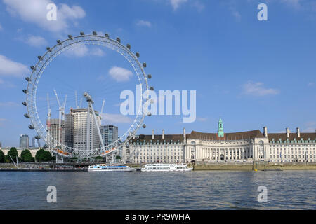 Westminster, London, UK - June 8, 2018:  Face on view of the complete London Eye and County Hall beside it. two boats moored at the river bank. - Stock Photo
