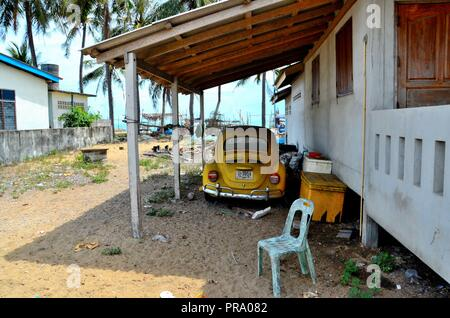 Classic German Volkswagen Beetle yellow car parked under shelter in Pattani Thailand - Stock Photo