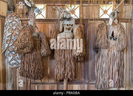 Collection of traditional grass skirts indigenous women wear hanging on a wall. Wamena, Papua, Indonesia. - Stock Photo