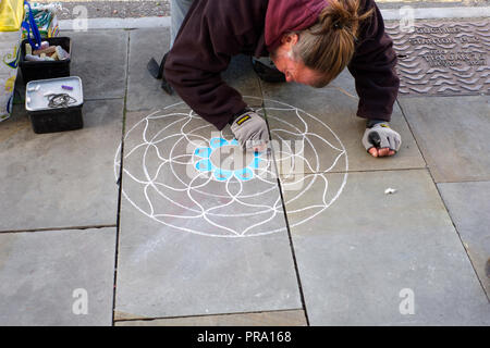 Artist beginning to make his Mandala on the pavement. Glastonbury, Somerset, UK - Stock Photo