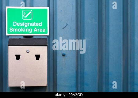 Designated smoking area sign and metal ash tray at work business wall - Stock Photo