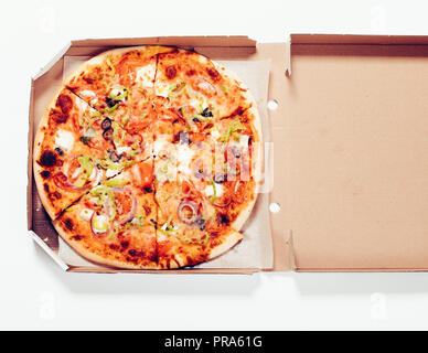 Close-up round baked pizza in open cardboard box on white background, top view. - Stock Photo