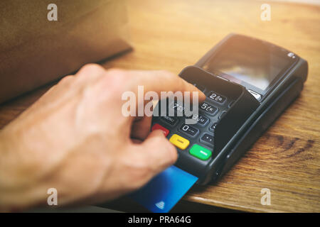 hand entering pin code on payment terminal at shop - Stock Photo