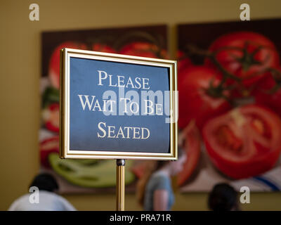 Please wait to be seated sign standing at the front of a restaurant  - Stock Photo