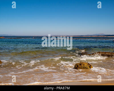 Waves crashing on rocks at a tropic beach with seaweed - Stock Photo