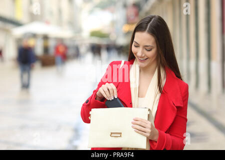 Happy woman in red taking out the phone from the bag in the street in winter - Stock Photo