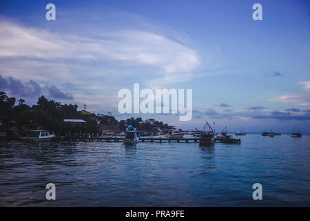 Sunset over boats lined up at the docks of Lívingston, a Garifuna Caribbean town in east Guatemala - Stock Photo