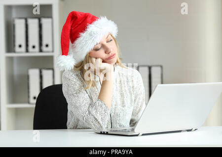 Bored employee working on line at office in christmas time - Stock Photo