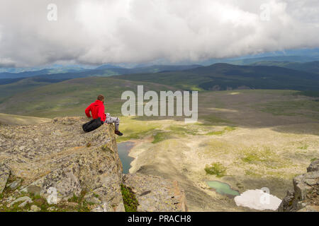 Guy travel in a red sweatshirt with a backpack is dangerously sits on a rock cliff dangling his legs down holding on to rocks in front of him is a col - Stock Photo