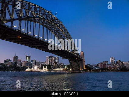 View of Sydney Harbour Bridge taken after sunset at blue hour with Luna Park in the background - Stock Photo