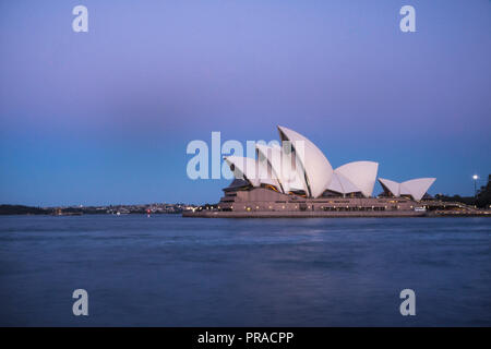View of Sydney Opera House taken at dusk during blue hour with the setting sun casting a beautiful bluish hue around the iconic landmark. - Stock Photo