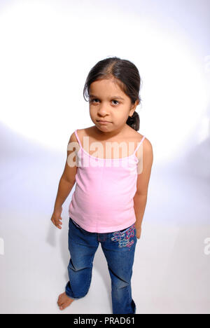 YOUNG GIRL FROWNING SHOT AGAINST A PLAIN BACKGROUND - Stock Photo