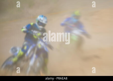 Blurry image of motorcycle riders during motocross race - Stock Photo