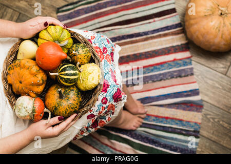 Young woman in white dress holding a basket with decorative pumpkins on her lap.