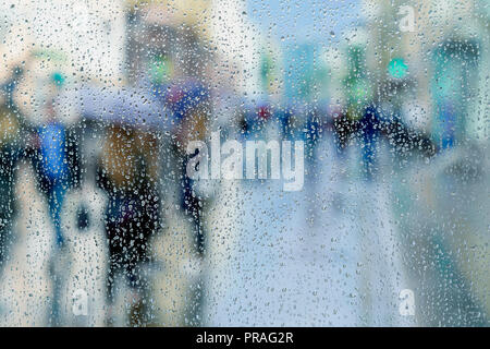 Rain drops on wet window, blurred people, city light bokeh. Concept of rainy weather, seasons, modern city. Copy space, for abstract background - Stock Photo