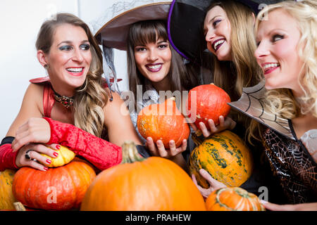 Four beautiful women acting as witches joining their malicious forces - Stock Photo