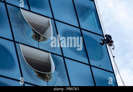 28 September 2018, Hamburg: A window cleaner is working on the facade of the Elbphilharmonie. Three times a year the glass facade of the Elbphilharmonie is cleaned by industrial climbers in a spectacular action. Photo: Axel Heimken/dpa - Stock Photo