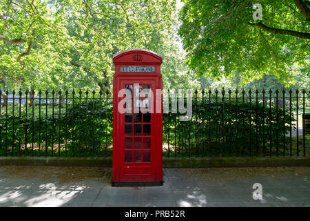 Typical red English telephone booth in the park. London, UK - Stock Photo