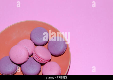 Macaroni on a gently pink background. Delicious cakes for tea. Dessert close-up. Bakery products. - Stock Photo