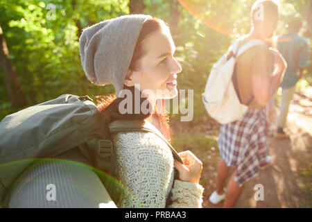 Young pretty camper with backpack talking to one of friends on their way to camp - Stock Photo
