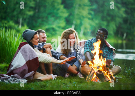 Several young backpackers sitting by campfire by waterside and warming their hands - Stock Photo