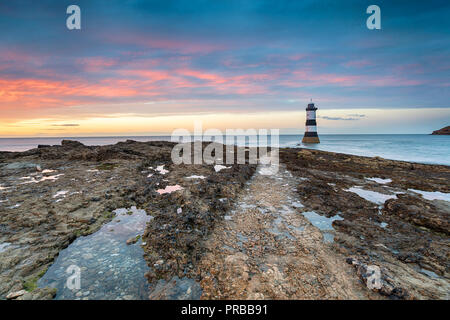 A beautiful sunset at Trwyn Du lighthouse on Penmon Point near Beaumaris on Anglesey in Wales - Stock Photo