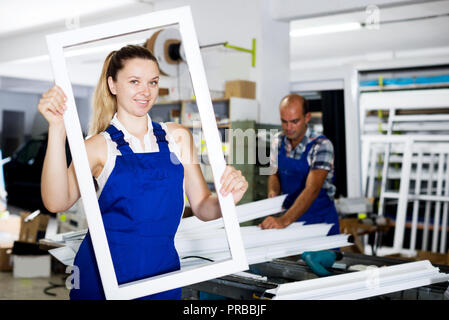 Smiling girl in blue overalls fun posing with window frame in factory - Stock Photo