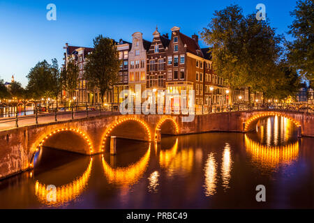 Amsterdam canal Illuminated bridges over the Keizersgracht canal and Leidsegracht canal Amsterdam canals Holland the Netherlands EU Europe - Stock Photo