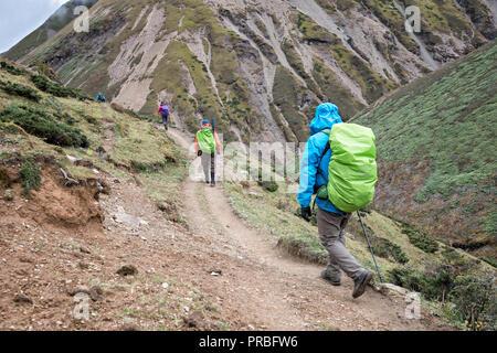 Trekkers on the trail to Lingshi down from Nyile La pass, Thimphu District, Snowman Trek, Bhutan - Stock Photo