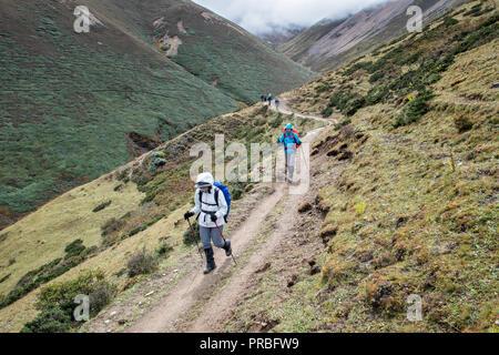 Trekkers on the way to Lingshi down the Nyile La pass, Thimphu District, Snowman Trek, Bhutan - Stock Photo