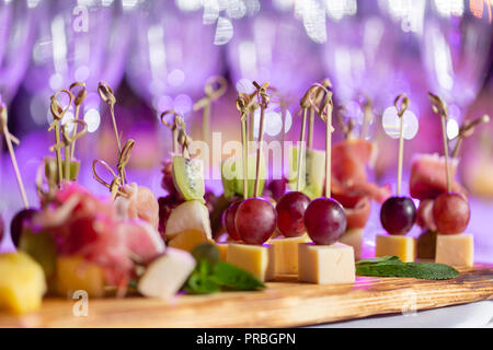 the buffet at the reception. Assortment of canapes on wooden board. Banquet service. catering food, snacks with cheese, jamon, prosciutto and fruit - Stock Photo