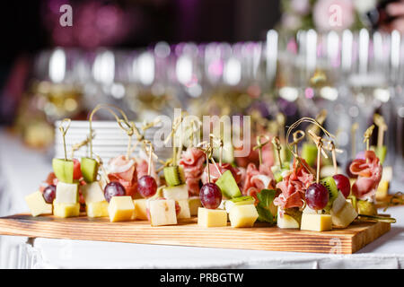 the buffet at the reception. Glasses of wine and champagne. Assortment of canapes on wooden board. Banquet service. catering food, snacks with cheese, jamon, prosciutto and fruit - Stock Photo