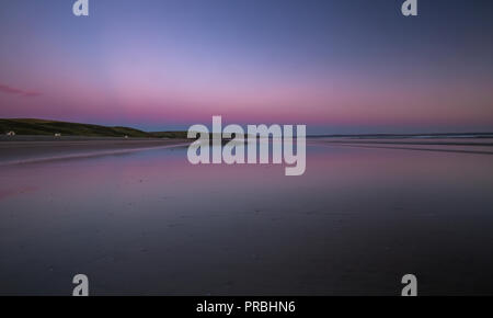 Colorful twilight sky over sandy beach at low tide in Newgale, Pembrokeshire, UK - Stock Photo