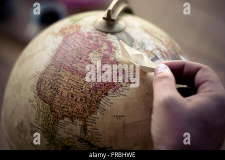 female dreamer wanderlust people hand playing with little paper boat on a globe world sphere chosing and imaginating to travel and arrive to a new des - Stock Photo