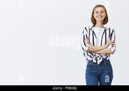 Successful female lawyer performing speech in front of students. Carefree woman with short blond hair, holding hands crossed in confidence pose and smiling broadly, feeling strong and self-assured - Stock Photo