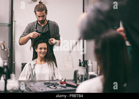 Young woman getting new hairstyle at professional hair styling saloon. - Stock Photo