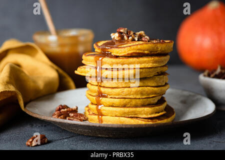 Pumpkin pancakes with caramel sauce and pecan nuts, black concrete background. Closeup view, selective focus - Stock Photo