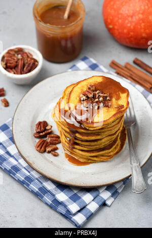 Pumpkin pancakes with caramel sauce, cinnamon and pecan nuts. Vertical, selective focus - Stock Photo