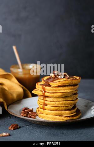 Pumpkin pancakes with caramel sauce. Thanksgiving day breakfast. Tasty american pumpkin pancakes - Stock Photo
