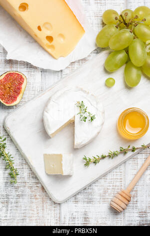Brie or camembert cheese served with fruits and honey on white cheeseboard. Top view - Stock Photo